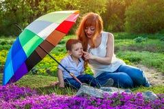 Jeune mère détendant avec son petit fils dans le jardin Concept de jour du ` s de mère Photos libres de droits