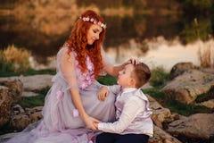 Jeune mère dans une robe féerique avec son fils près de la rivière au coucher du soleil Photographie stock