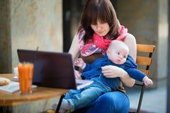 Jeune mère de fonctionnement avec son fils dans un café photo libre de droits