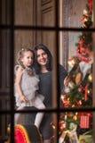 Jeune mère de sourire avec la petite fille mignonne près d'un arbre de Noël Concept étonnant de vacances de famille Images stock