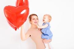 Jeune mère de sourire avec la petite fille sur des mains Photo libre de droits