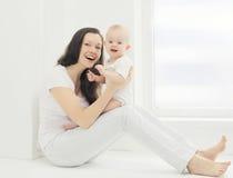 Jeune mère de sourire heureuse avec le bébé à la maison dans la chambre blanche Photos libres de droits