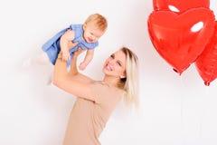 Jeune mère de sourire tenant la petite fille riante sur des mains, Image libre de droits