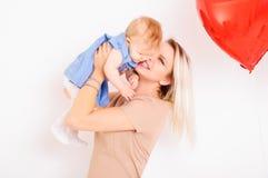 Jeune mère de sourire tenant la petite fille sur des mains Photos stock