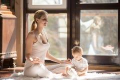 Jeune mère de yogi dans la pose facile de Seat, fille de bébé près Photos stock