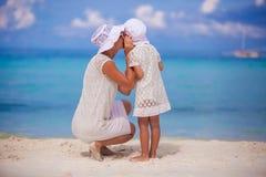 Jeune mère disant un secret à l'oreille de elle photographie stock
