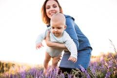 Jeune mère en nature avec le fils de bébé dans les bras Image stock