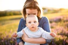 Jeune mère en nature avec le fils de bébé dans les bras Image libre de droits