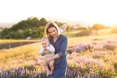 Jeune mère en nature avec le fils de bébé dans les bras Photographie stock libre de droits