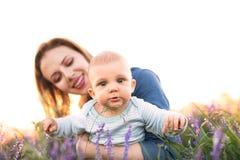 Jeune mère en nature avec le fils de bébé dans les bras Photographie stock