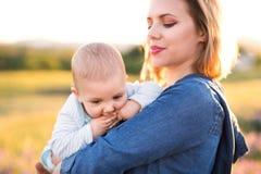 Jeune mère en nature avec le fils de bébé dans les bras Images stock