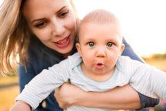 Jeune mère en nature avec le fils de bébé dans les bras Photos stock