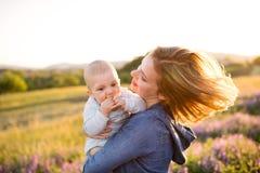 Jeune mère en nature avec le fils de bébé dans les bras Photo stock