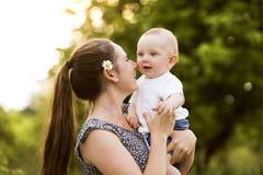 Jeune mère en nature tenant le petit fils de bébé dans les bras Photographie stock libre de droits