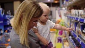 Jeune mère en verres tenant son enfant dans des ses bras tout en choisissant des biscuits sur les étagères dans le supermarché banque de vidéos