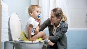 Jeune mère enseignant ses 2 années de garçon d'enfant en bas âge employant la toilette Images stock