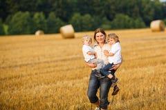 Jeune mère et deux petits garçons de jumeaux ayant l'amusement sur le foin jaune Photographie stock libre de droits