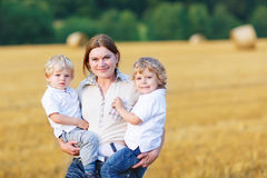 Jeune mère et deux petits garçons de jumeaux ayant l'amusement sur le foin jaune Image libre de droits