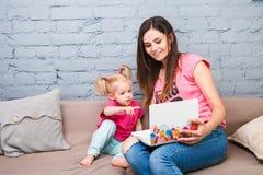 Jeune mère et fille de deux ans avec les cheveux blonds se reposant sur le divan et à l'aide de l'ordinateur portable Ils sont ha photos stock