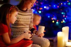Jeune mère et filles s'asseyant par une cheminée sur Noël Photo libre de droits
