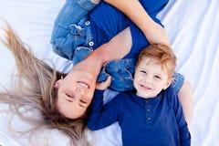 Jeune mère et fils souriant et recherchant - s'étendant sur le Ba blanc Image libre de droits