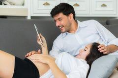 Jeune mère et mari de famille asiatique de couples à l'aide d'un comprimé Photo libre de droits