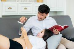 Jeune mère et mari de famille asiatique de couples à l'aide d'un comprimé Photographie stock libre de droits