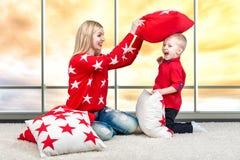 Jeune mère et petit fils jouant avec des oreillers, combat d'oreiller Le concept des vacances de famille Beaux oreillers pour déc image stock