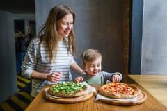 Jeune mère et petit fils mignon manger de la pizza dans le restaurant photographie stock