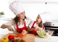 Jeune mère et petite fille à la cuisine de maison préparant la salade pour le tablier de déjeuner et le chapeau de port de cuisin Image stock