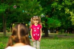 Jeune mère et petite fille jouant en parc avec des bulles de savon Photo stock