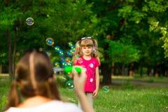 Jeune mère et petite fille jouant en parc avec des bulles de savon Image stock