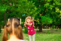 Jeune mère et petite fille jouant en parc avec des bulles de savon Photo libre de droits