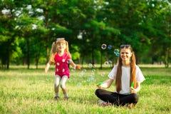 Jeune mère et petite fille jouant en parc avec des bulles de savon Images libres de droits