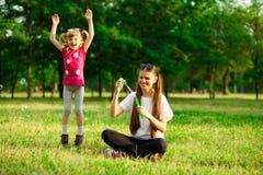 Jeune mère et petite fille jouant en parc avec des bulles de savon Image libre de droits