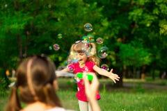Jeune mère et petite fille jouant en parc avec des bulles de savon Photographie stock libre de droits
