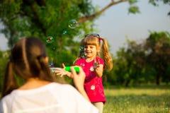 Jeune mère et petite fille jouant en parc avec des bulles de savon Images stock