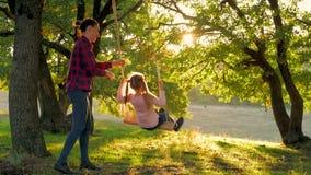 Jeune mère et sa fille d'enfant balançant sur les oscillations et riant égaliser chaud d'automne dehors Aimer heureux clips vidéos