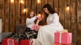 Jeune mère et sa fille jouant heureusement avec des jouets le réveillon de Noël Image stock
