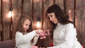 Jeune mère et sa fille jouant heureusement avec des jouets le réveillon de Noël Image libre de droits