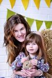 Jeune mère et sa fille souriant et tenant un lapin Photographie stock