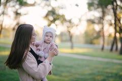 Jeune mère et sa petite fille de bébé ayant l'amusement dans un parc photographie stock libre de droits