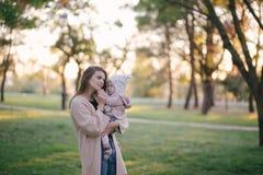 Jeune mère et sa petite fille de bébé ayant l'amusement dans un parc image stock