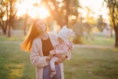 Jeune mère et sa petite fille de bébé ayant l'amusement dans un parc photos stock