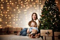 Jeune mère et ses filles près de l'arbre de Noël photo stock