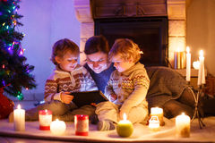 Jeune mère et ses petits enfants s'asseyant par une cheminée sur C image libre de droits
