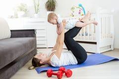 Jeune mère et son bébé garçon faisant le yoga sur le plancher au salon Photo stock