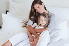 Jeune mère et son descendant posant sur un bâti Photo libre de droits