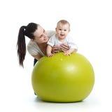 Jeune mère et son enfant de bébé faisant des exercices de yoga sur la boule gymnastique d'isolement au-dessus du blanc Photographie stock