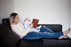 Jeune mère et son enfant lisant un livre, le concept du développement précoce, d'intérieur Image stock
